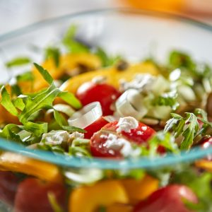 Close-up healthy salad from pepper, arugula, leek, tomato and cheese in a transparent bowl on a gray