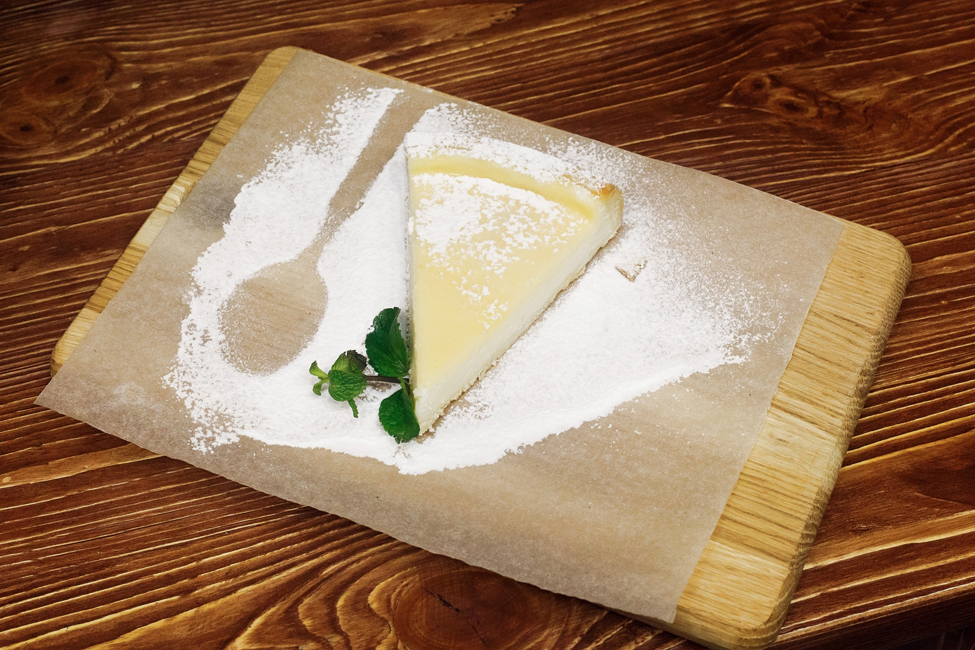 Delicious cheesecake with powder and mint serving on wooden desk