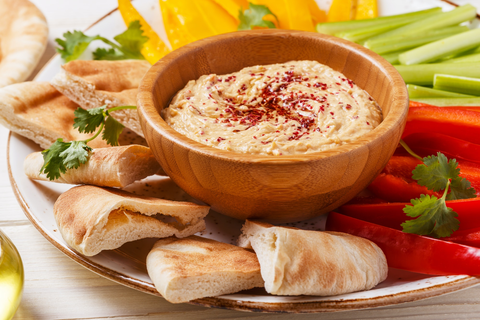 Homemade hummus with assorted fresh vegetables and pita bread.