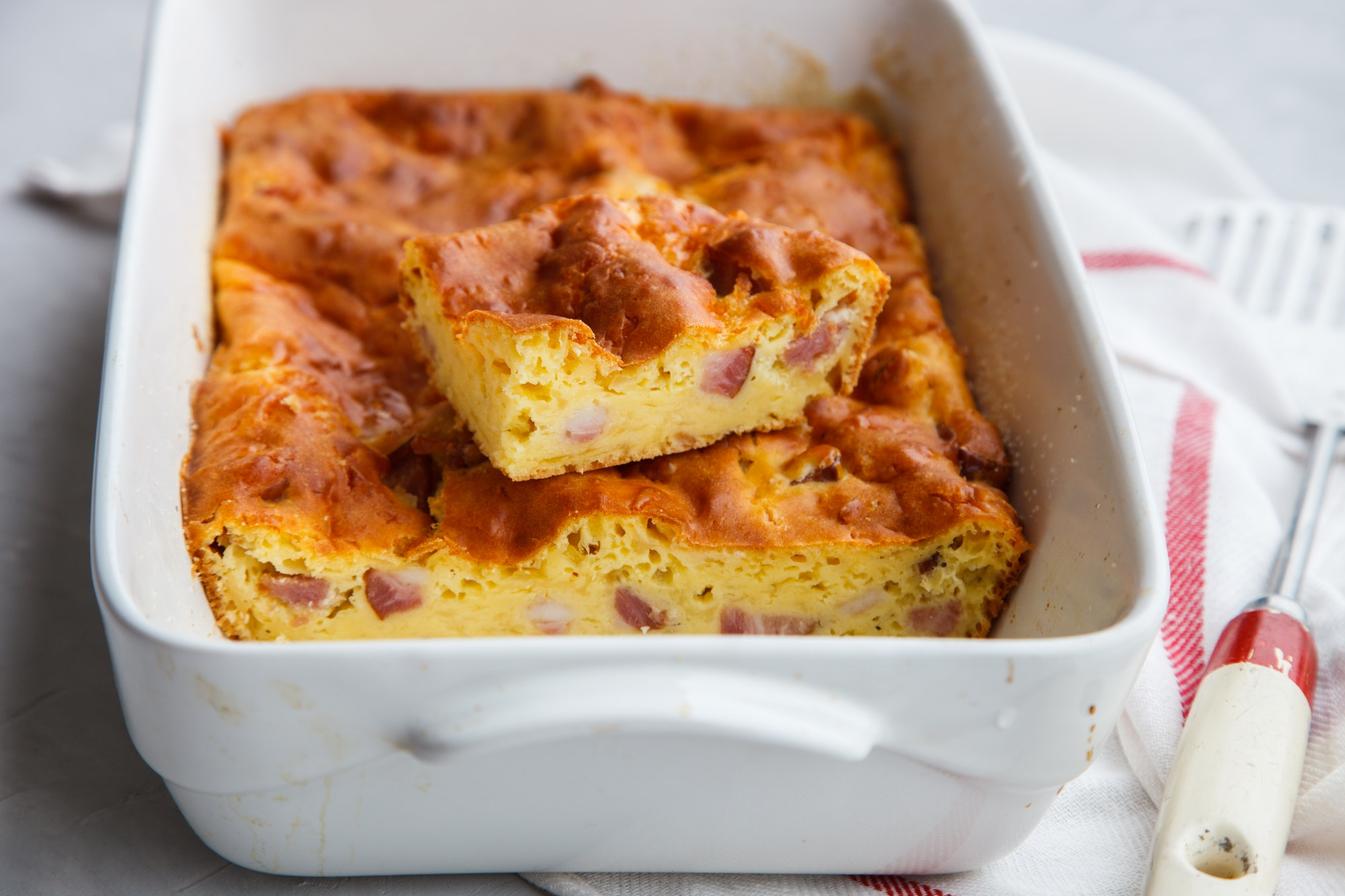 Pie with cheese and ham in baking dish